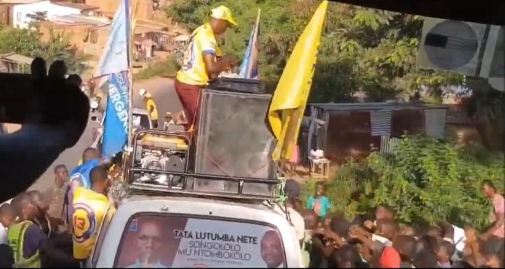 Le slogan de campagne de Lutumba Simarro affiché sur la lunetter arrière d'un minibus.