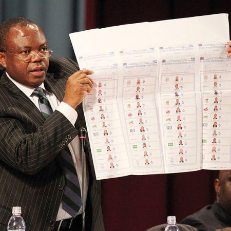 Corneille Nanga président de la CENI montrant un bulletin de vote